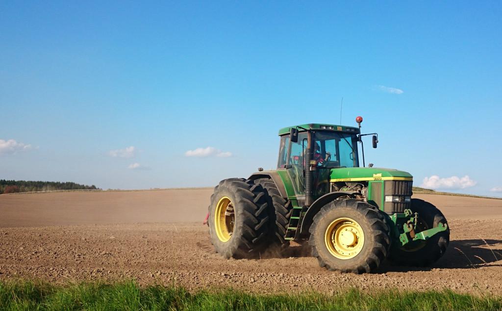 Bilden visar en traktor körandes på en åker