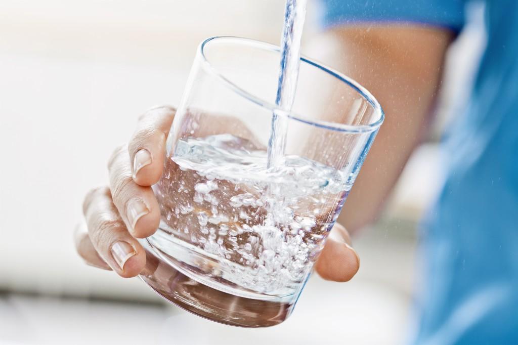 Bilden beskriver hur en person fyller ett glas med vatten