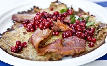 Bilden beskriver en maträtt betående av lingon, bacon pch rårakor