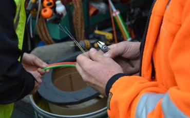 Händer installerar fibernät.
