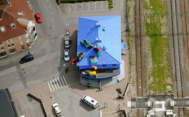 Bilden föreställer ett flygfoto på Vara resecentrum. En blå byggnad med konstverk på taket