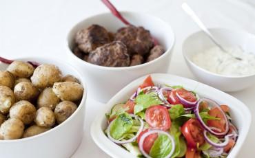 Fyra skålar med mat. En med potatis, en med biffar, en med sallad och en med sås.