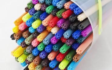 Bilden visar en plastburk med färgpennor.