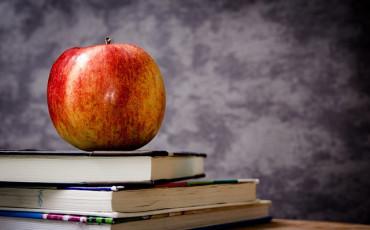 Böcker med ett rött äpple på