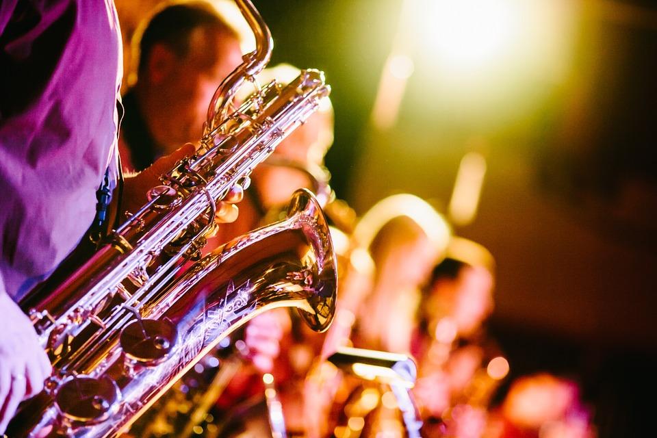 Saxofon i närbild och flera som spelar instument längre bort i bilden