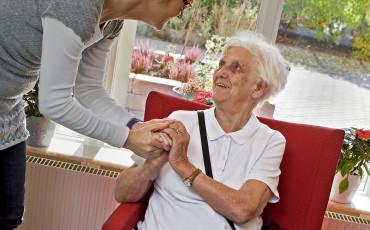 Två kvinnor håller varandras händer