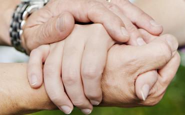 Händer håller om varandra och erbjuder stöd.