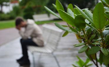En person sitter på en bänk med huvudet lutat i sina händer