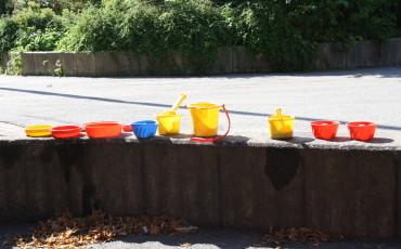 Bilden visar en sandlåda med färgglada sandleksaker.