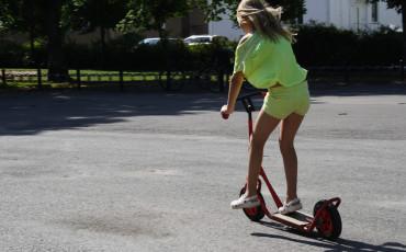 Flicka som åker på en sparkcykel