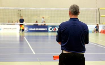Ryggtavlan av en man med en domarflagga framför en badmintonplan.