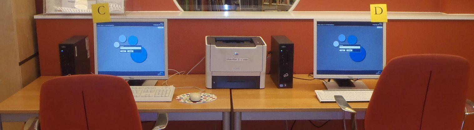 Bord med två datorer och skrivare samt två kontorsstolar