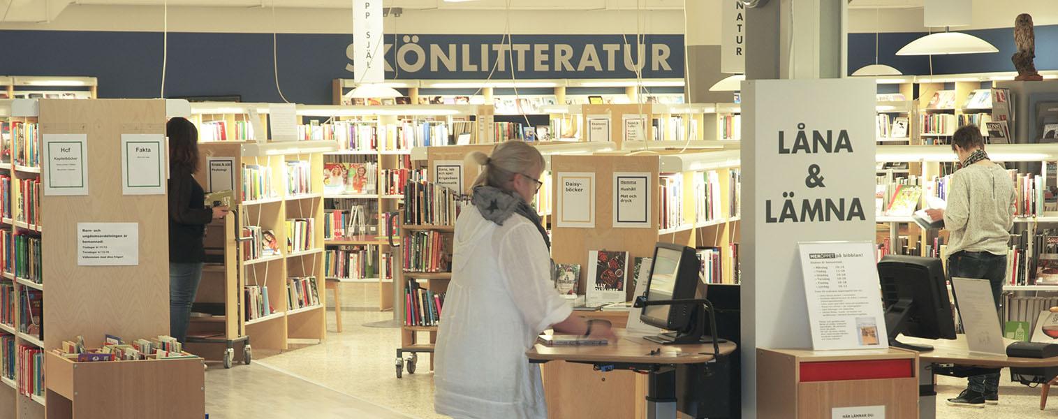 Vy över biblioteket Vara med bokhyllor och människor som tittar i böcker