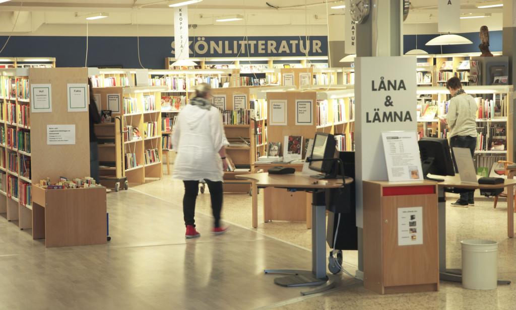 Interiörbild från Vara bibliotek. Bokhyllor, utlåningsautomater och tre människor i lokalen.