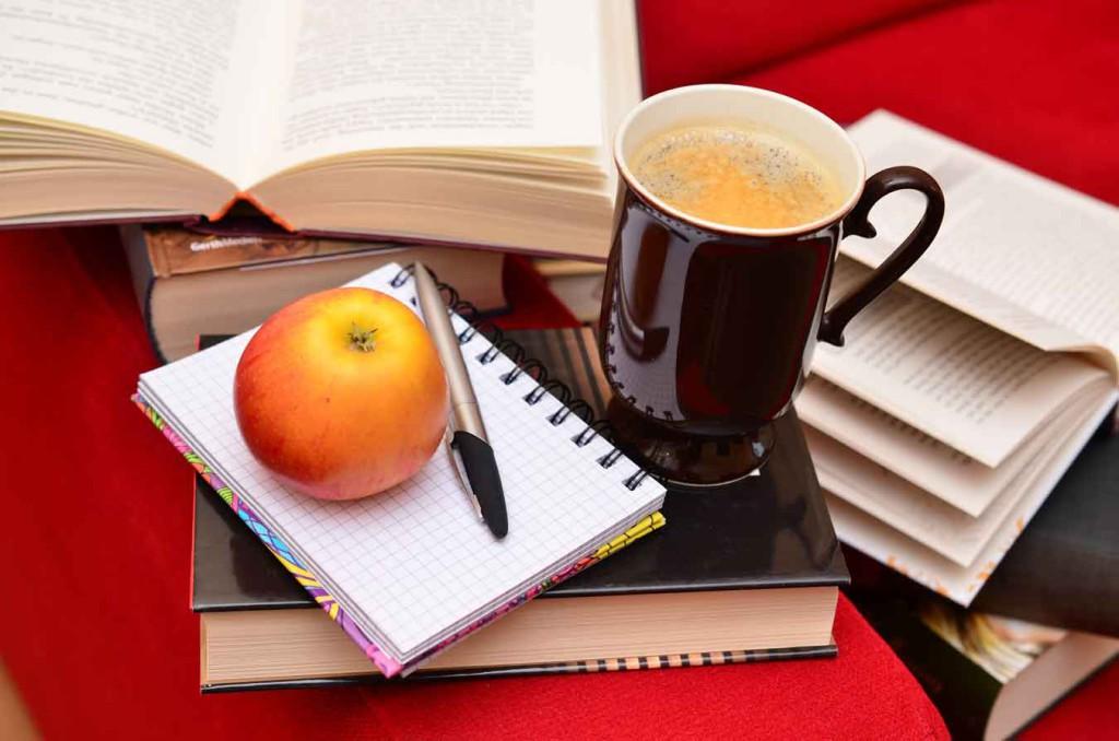 En hög med böcker med ett äpple och en penna på