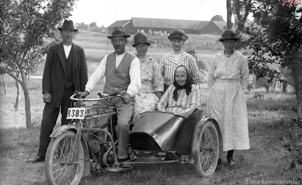 Fotografi från tidigt 1900-tal med 6 personer i tidstypiska kläder och en motorcykel med sidovagn
