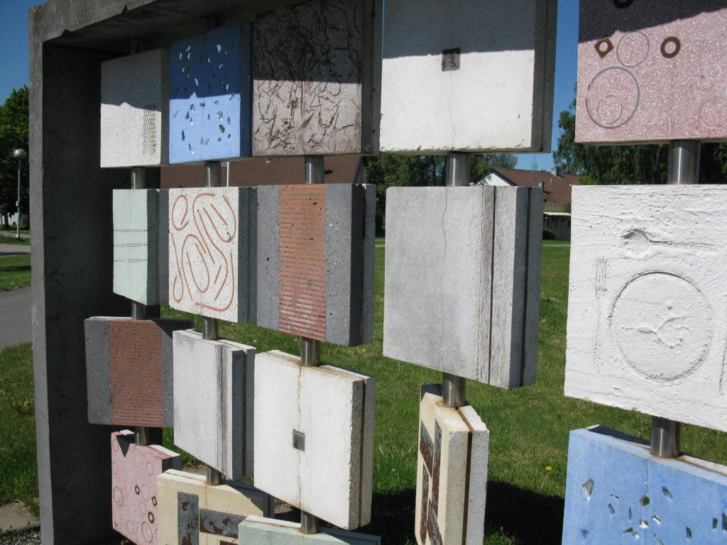 Betongplattor på stålstänger lodrätt monterade i en stålram framför en gräsmatta. Konstverket The Sampler.