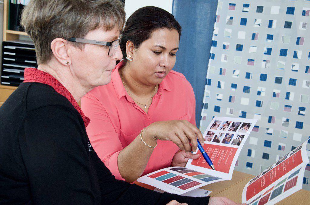 Bilden visar två kvinnor som tittar i en informationsfolder.