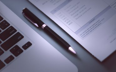Bilden visar en penna som ligger mellan en dator och ett papper