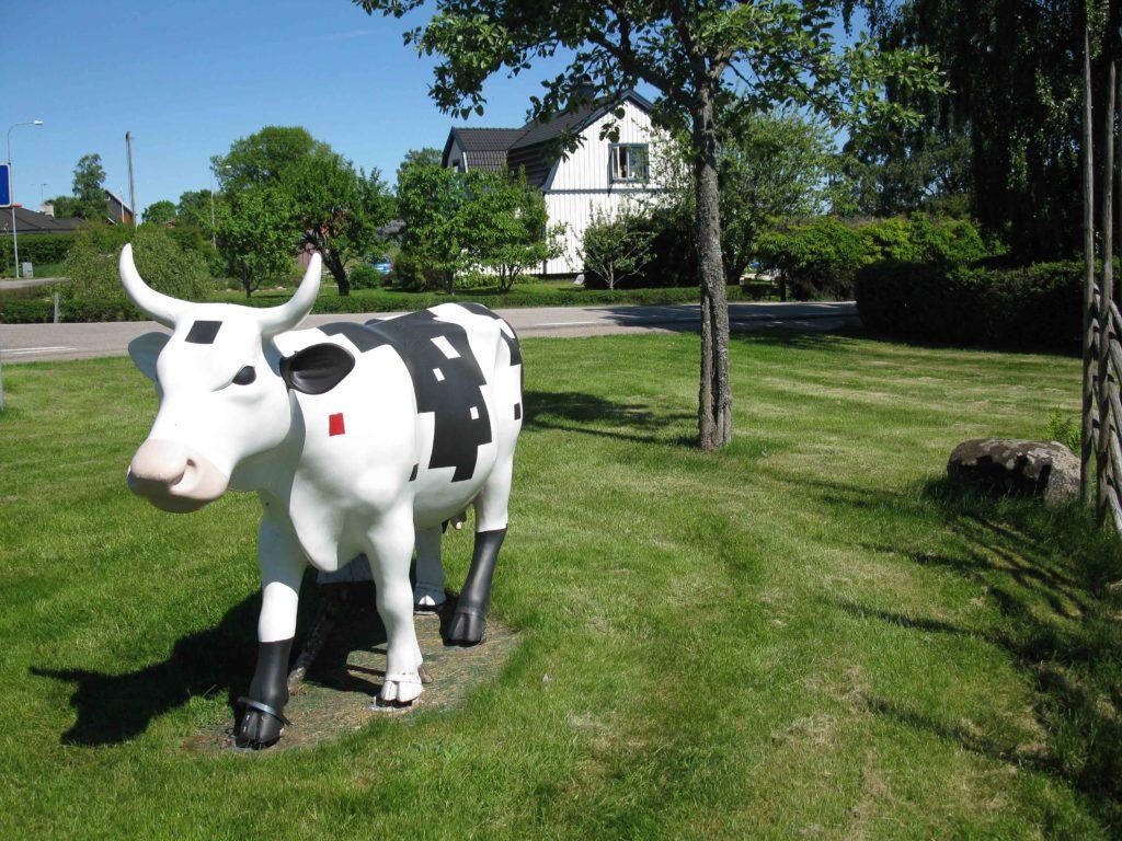 Skulptur föreställande en ko på en gräsmatta. Konstverket Kobism av Lasse Åberg.