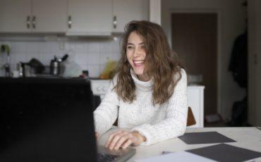 Bilden föreställer en tjej som sitter hemma med sin dator