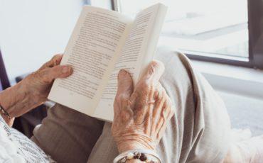 En äldre persons händer som håller i en uppslagen bok