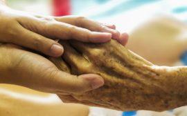 En yngre person håller en äldre i handen.
