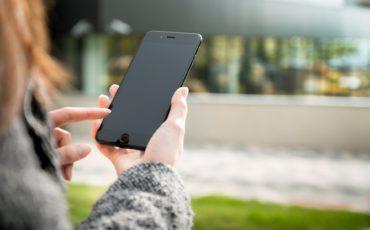 Bilden visar en person som tittar på sin mobil