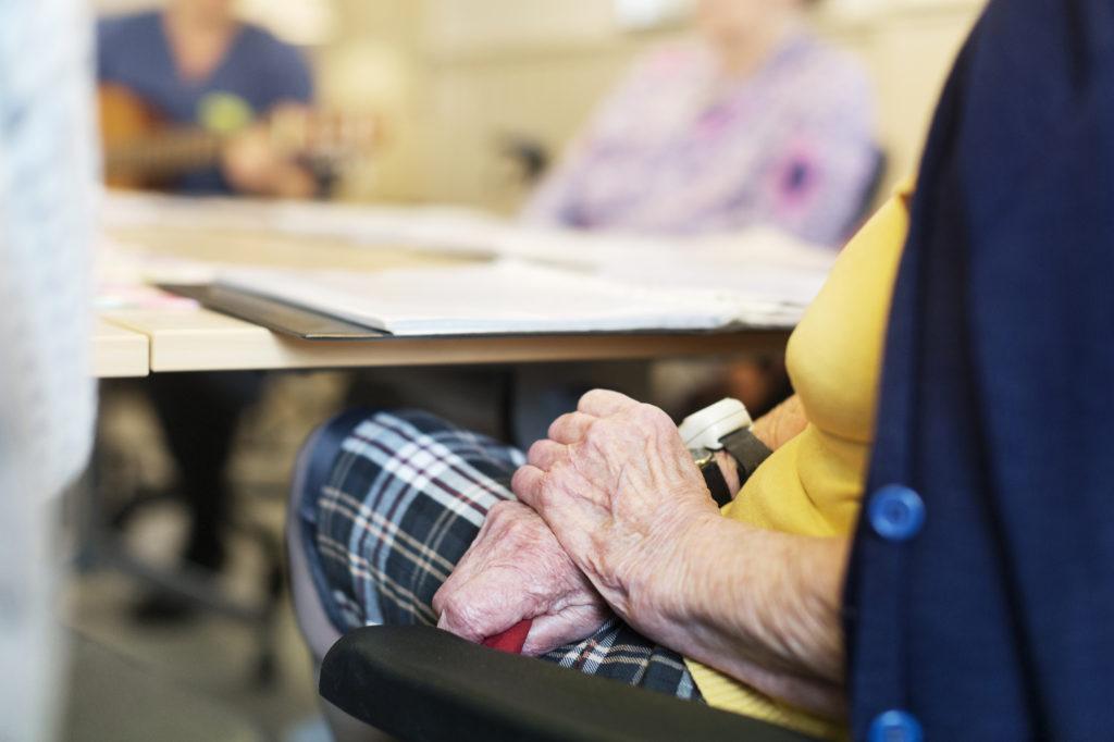 Äldre person sitter vid bord med korsade händer.