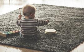 Bebis sittandes på grå matta med xylofon och tamburin.