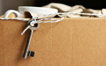 Bilden föreställer en flyttkartong med en nyckel hängande i ett snöre.