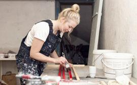 Bilden visar en elev i snickarbyxor som målar träbitar vid ett arbetsbord