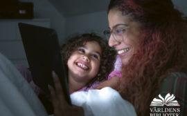 Ett barn och en kvinna tittar på en läsplatta ihop och ser glada ut.