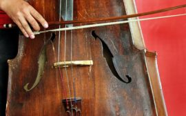 Bild på mittenpartiet av en cello, en hand håller i en stråke