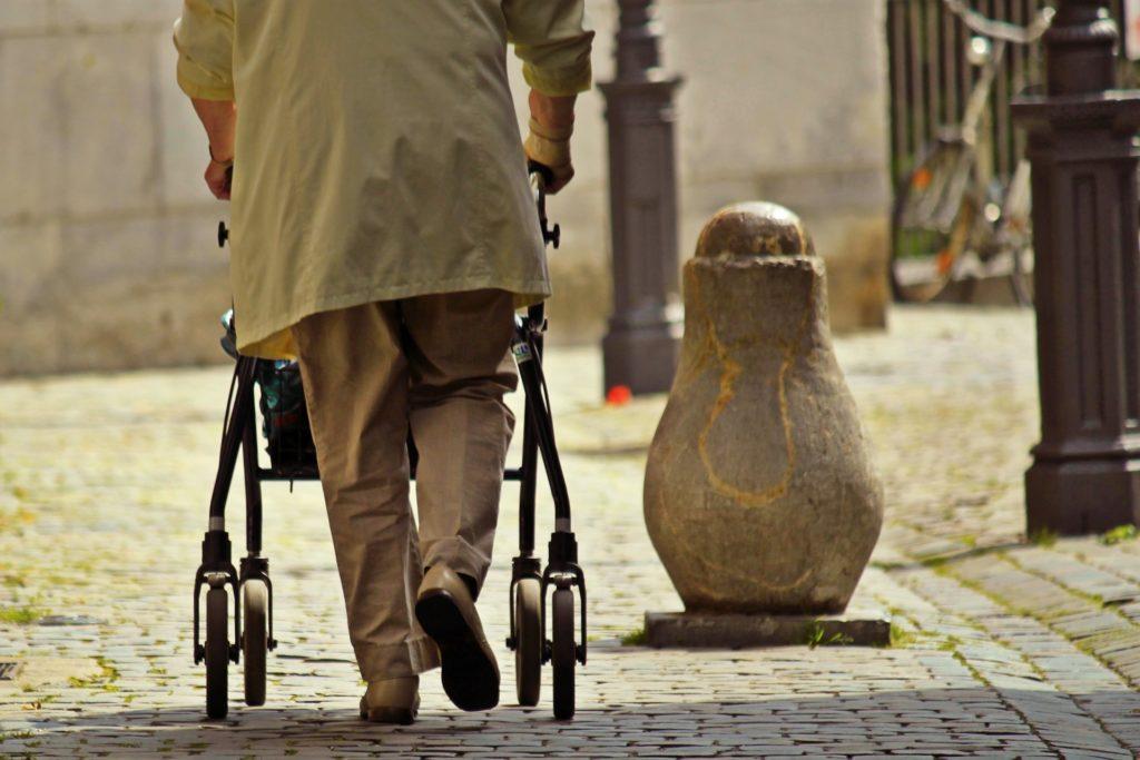 Pensionär med rullator på promenad.