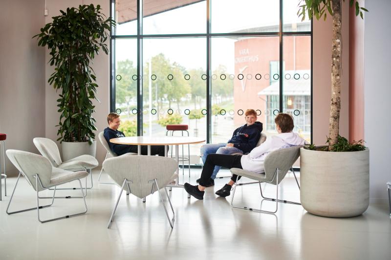 Tre elever på Lagman sitter och pratar på sin rast.