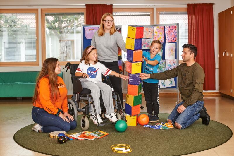 Tre elever på barn- och fritidsprogrammet bygger med klossar med två barn.