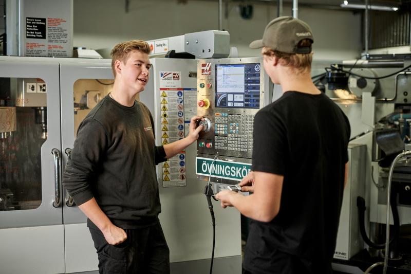 Två elever på industriprogrammet vid en maskin.