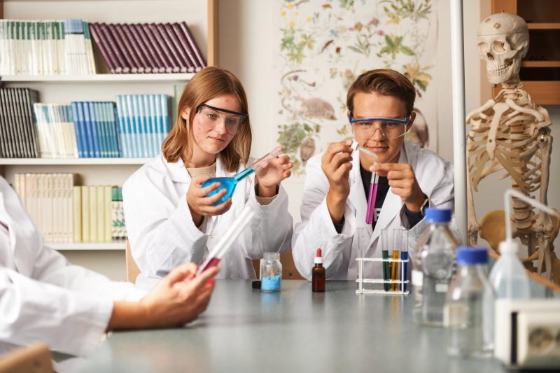 Två elever på Naturprogrammet visar ett experiment.