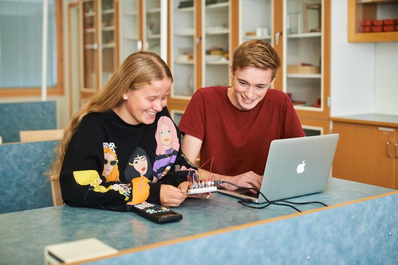 Två elever på Teknikprogrammet sitter i ett klassrum framför en dator.