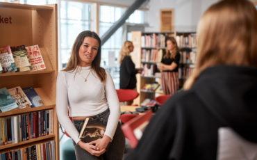 Några elever och personal samtalar i biblioteket Lagman