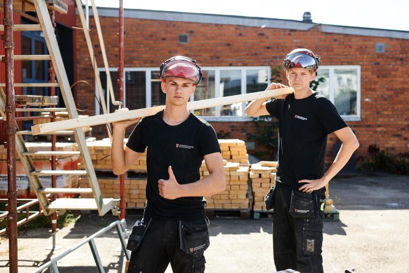 Två elever från byggprogrammet bär på en bräda.