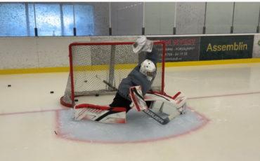 En målvakt i målet på ishockeyplan