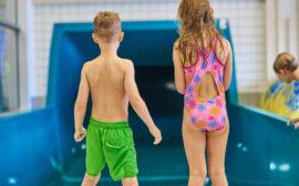 Bilden föreställer två barn i ett badhus.