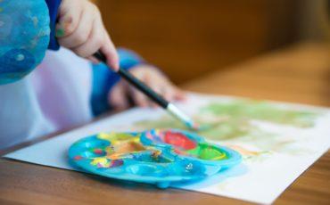 Ett papper och en palett med nånga olika färger på ett bord. En hand håller i en pensel.