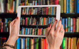 Två händer som hller i en läsplatta framför en bokhylla med böcker. På skärmen visas böckerna i bokhyllan.