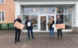 Fyra personer står framför kommunhuset i Vara, två av dem håller i stipendium.