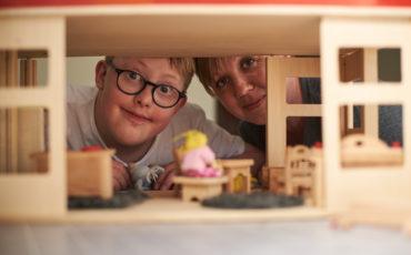 En pojke och en kvinna tittar fram bakom ett dockhus.
