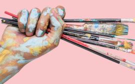 Bilden föreställer en hand med målarpenslar.