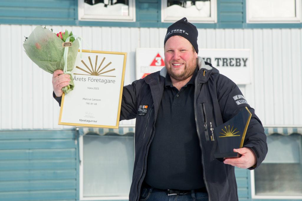 Man håller upp blommor och diplom vid en prisutdelning.